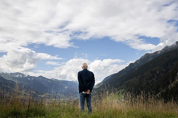 Matthias Horx steht mit dem Rücken zum Betrachter und schaut auf ein Tal herab.