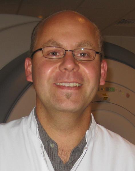 Portraitfoto von Dr. Hagen Kitzler vor einem MRT Scanner